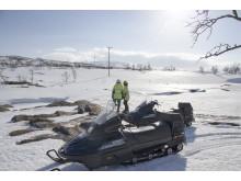Oskar och Stig bedömer om isen över älven håller för att köra över med skotrarna.