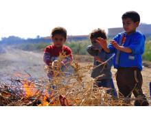 Barn värmer sig över eld