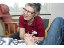 Inger Olofsson från Röda korset håller en hand på Medicinkliniken Danderyds sjukhus.