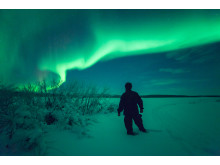 Northern Lights Watcher on Frozen Lake