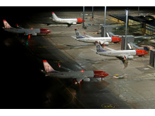 Several Norwegian aircraft parked at Oslo Airport Gardermoen at night