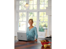 Woman smiling and standing at kitchen counter using HP laptop
