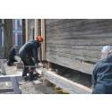 Restaurering Måketorpsboden – skadat väggtimmer lyfts bort